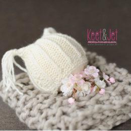 Knitted newborn bonnet staartje